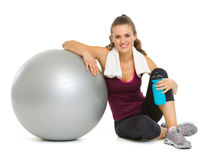 Happy fitness woman sitting near fitness ball Stock Photography
