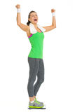 Happy fitness young woman standing on scales Stock Photo