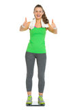 Happy fitness young woman standing on scales Royalty Free Stock Photography