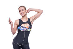 Happy fitness young woman wearing sportswear tracksuit with earphones is listening to music using a smartphone. Royalty Free Stock Photo
