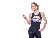 Happy fitness young woman wearing sportswear tracksuit with earphones is listening to music using a smartphone. Royalty Free Stock Images