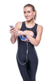 Happy fitness young woman wearing sportswear tracksuit with earphones is listening to music using a smartphone. Stock Photos