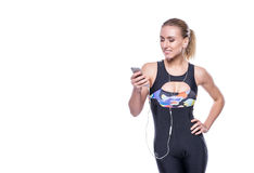 Happy fitness young woman wearing sportswear tracksuit with earphones is listening to music using a smartphone. Copyspace. Royalty Free Stock Images