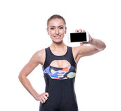 Happy fitness young woman wearing sportswear tracksuit showing blank smartphone screen isolated on white background. Stock Images
