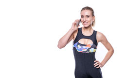 Happy fitness young woman wearing sportswear tracksuit is talking on the phone isolated on white background. Copyspace for text. Royalty Free Stock Images