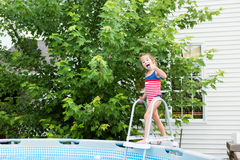 Happy five year old girl entering swimming pool royalty free stock photography