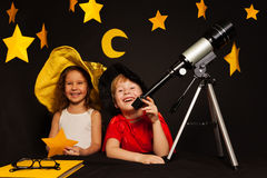 Happy five years old kids playing sky watchers. Happy five years old kids, boy and girl playing sky watchers stargazing with telescope Royalty Free Stock Photos