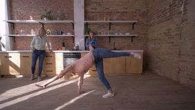 Happy flexible girl makes gymnastic somersault in front of mom and sister in the kitchen at home stock video footage