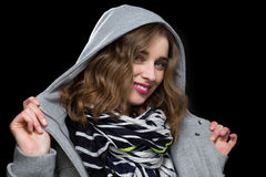 Happy flirtatious woman in a hooded jacket. Smiling playfully at the camera as she twirls the collar in her hands on a dark background stock photography