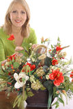 Happy florist making flower arrangement. Isolated on a white background Royalty Free Stock Images