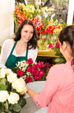 Happy florist making roses bouquet women customer. Happy florist making roses bouquet woman customer buying flower shop royalty free stock images