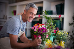 Happy florist preparing a flower bouquet Royalty Free Stock Images
