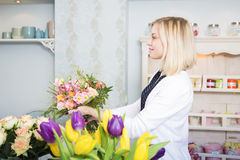 Happy florist presents the boquet to her client Stock Photo