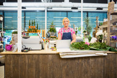 Happy Florist Standing At The Counter Of Flower Store stock photography