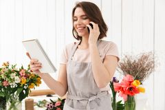 Happy florist woman in apron working in flower shop, and speakin. Happy florist woman in apron working in flower shop and speaking on cell phone while holding Royalty Free Stock Photography