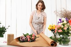 Happy florist woman working with flowers in workshop. Photo of happy florist woman standing near table working with flowers in workshop Stock Photos