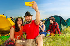 Happy flower-adorned couple making selfie at camp. Portrait of young happy flower-adorned couple making picture with a phone camera Stock Photography