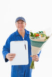 Happy flower delivery man showing clipboard Royalty Free Stock Photography