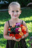 Happy Flower Girl. A beautiful child loves holding her colorful bouquet of flowers Stock Photo