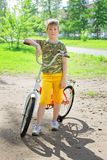 Happy flushed boy teen finished training on the bike. A teenager boy posing near his favorite bicycle in a summer park. Joy from active rest during the holidays stock photography