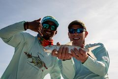 Free Happy Fly Fisherman With Belizean Guide Shows Off The Bonefish He Caught Stock Image - 165498111