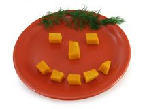 Happy food - pumpkin smiley. Smiley made of pumpkin pieces on a red plate with dill hair royalty free stock photo