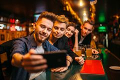 Happy football fans makes selfie at bar counter. Happy football fans makes selfie on phone camera at the bar counter in a sport pub, victory celebration royalty free stock photography