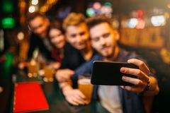 Happy football fans makes selfie at bar counter. Happy football fans makes selfie on phone camera at the bar counter in a sport pub stock image