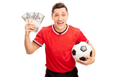 Happy football player holding a ball and money Royalty Free Stock Photos