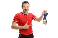 Happy football player holding gold medals and pointing Stock Photos