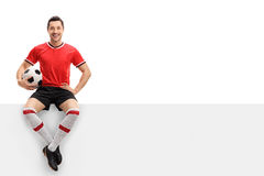 Happy football player sitting on a panel Stock Photos