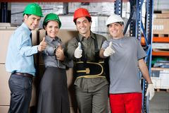Happy Foremen And Supervisors Gesturing Thumbs Up. Portrait of happy foremen and supervisors gesturing thumbs up at warehouse - shallow depth of field, focus on Royalty Free Stock Photos