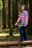 A happy forester with an ax near the dumped tree. In the forest smiles Royalty Free Stock Image