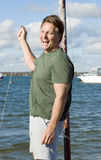 Happy forties man. A handsome forties man is standing in a dinghy on the sea shore and laughing Royalty Free Stock Images