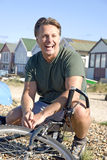Happy forties man. A handsome forties man is crouching down with his mountain bike during a day out at the beach Stock Photo