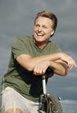 Happy forties man. A healthy fit forties man leans on his bike and smiles during a day out cycling Royalty Free Stock Photos