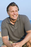 Happy forties man. A happy smiling forties man is enoying himself on a beach during his vacation Stock Photo