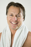 Happy forties man. A happy smiling forties man  has a towel wrapped around his neck after taking a shower Royalty Free Stock Image