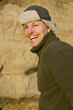 Happy forties man. A happy laughing forties man wearing a trendy hat is enjoying a beautiful winter`s day on the beach Royalty Free Stock Image