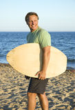 Happy forties man. A handsome forties man is smiling as he walks along a beautiful sandy beach carrying his skimboard Royalty Free Stock Images