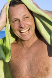 Happy forties man. A happy laughing forties man is fooling around with his beach towel on the beach Stock Photo