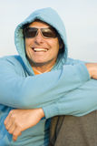 Happy forties man. A portrait of a happy smiling forties man wearing a hooded blue top and stylish glasses Royalty Free Stock Images