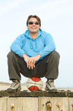 Happy forties man. A portrait of a happy smiling forties man wearing a hooded blue top and stylish glasses,He is sitting on a basketball while having fun at the Stock Image