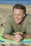 Happy forties man. A happy smiling forties man is laying on the beach and having fun Royalty Free Stock Photography