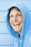 Happy forties man. A handsome laughing forties man wearing a blue hooded sweat top is having fun at the beach Royalty Free Stock Photos