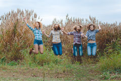Happy four teenage girls jumping and holding hands. Picture of four teenage girls jumping and holding hands. Happy friends in casual on fall outdoor background Royalty Free Stock Photos