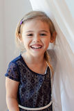 Happy four year old girl by sheer white curtain Stock Images