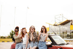 Happy four young women friends standing near car outdoors. Stock Photos