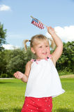 Happy Fourth of July. Adorable little blond girl in red white and blue waving the American flag Stock Image