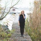 Happy free blonde woman enjoying fresh air at lakeside. Royalty Free Stock Photography